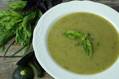 Soup with zucchini, basil and chives. In white bowl Stock Photos