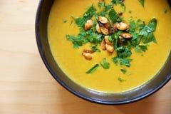 Soupe à carotte de Puréed dans la cuvette avec les graines et le persil de citrouille Image stock