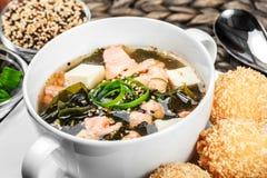 Soupe à fruits de mer avec les saumons, le fromage, l'algue, le sésame et le pain du plat sur le fond en bois photographie stock