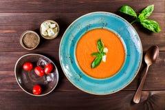 Soupe à gazpacho de tomate avec le basilic, le feta, la glace et le pain sur le fond en bois foncé, cuisine espagnole Ingrédients Photographie stock
