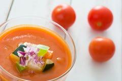 Soupe à Gazpacho en verre et ingrédients sur la table en bois blanche Photo libre de droits