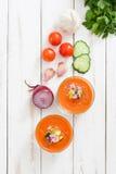 Soupe à Gazpacho en verre et ingrédients sur la table en bois blanche Photographie stock
