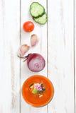 Soupe à Gazpacho en verre et ingrédients sur la table en bois blanche Photos libres de droits