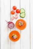Soupe à Gazpacho en verre et ingrédients sur la table en bois blanche Photographie stock libre de droits