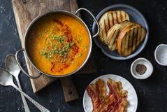 Soupe à lentille fumée de paprika avec les sandwichs grillés à fromage et le lard croustillant sur un fond foncé, vue supérieure  Image stock