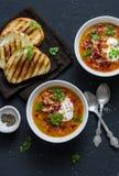 Soupe à lentille fumée de paprika avec les sandwichs grillés à fromage et le lard croustillant sur un fond foncé, vue supérieure  Photos stock