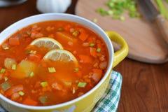 Soupe à mélange de Solyanka avec des saucisses, des pommes de terre et le citron Photographie stock libre de droits