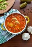 Soupe à mélange de Solyanka avec des saucisses, des pommes de terre et le citron Image libre de droits