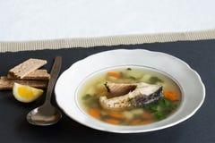 Soupe à poissons sur le fond en pierre noir Plat blanc de vintage avec les poissons, la pomme de terre, la carotte et les herbes  Images libres de droits