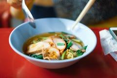 Soupe à porc cuite par vue courbe sur la table de salle à manger rouge photographie stock libre de droits