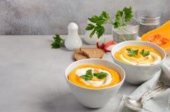 Soupe à potiron avec de la crème et le persil sur un fond concret ou en pierre gris Photo stock