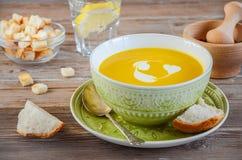 Soupe à potiron avec des croûtons de pain sur la table en bois Image stock