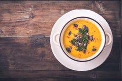 Soupe à potiron avec des graines de citrouille et des poivrons de piment photos stock