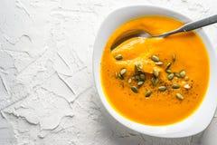 Soupe à potiron avec des graines et une cuillère dans un plat Photo stock