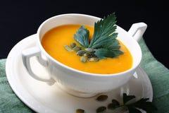 Soupe à potiron dans le plat blanc sur le fond noir Image libre de droits