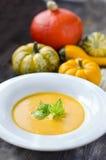 Soupe à potiron dans un plat avec des potirons Image stock
