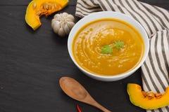 Soupe à potiron dans une cuvette avec les potirons, l'ail et le persil frais h Images stock