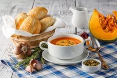 Soupe à potiron dans une cuvette avec les potirons, l'ail et le persil frais h Photos libres de droits