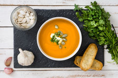 Soupe à potiron de plat d'ardoise et d'une table en bois blanche Photo libre de droits