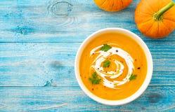 Soupe à potiron et à carotte avec le persil sur la vue supérieure de fond bleu photo libre de droits