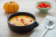 Soupe à potiron, potiron de Munchkin et une cuvette avec des poivrons Photos stock