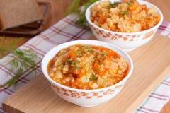 Soupe à tomate avec du riz et des légumes dans une casserole et un bre blancs Photo libre de droits