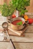 soupe à tomate avec le basilic dans un pot sur le marbre photos stock