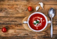 Soupe à tomate dans une cuvette blanche, tomates-cerises, ail Photographie stock libre de droits