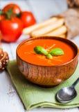 Soupe à Tomatoe avec des batons de pain et basilic sur le fond en bois Photo stock