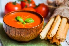 Soupe à Tomatoe avec des batons de pain et basilic sur le fond en bois photographie stock libre de droits