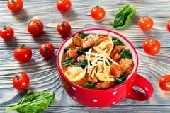 Soupe à Tortellini avec les saucisses italiennes, épinards, tomate, parmesan photo stock