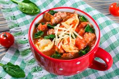 Soupe à Tortellini avec les saucisses italiennes, épinards, tomate, parmesan photos stock
