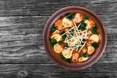 Soupe à Tortellini avec les saucisses italiennes, épinards, tomate, parmesan, dessus-vue photos libres de droits