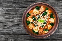Soupe à Tortellini avec les saucisses italiennes, épinards, tomate, parmesan, dessus-vue image stock