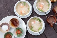 Soupe au riz thaïlandaise avec la crevette et le porc, assaisonnement, sauce à poissons, piment mariné, poivre de Cayenne, sucre Images libres de droits