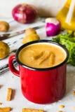 Soupe aux pois avec de la purée de pommes de terre dans la tasse rouge d'émail Photo libre de droits