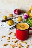 Soupe aux pois avec de la purée de pommes de terre dans la tasse rouge d'émail Photographie stock libre de droits