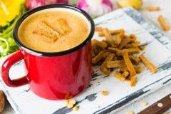 Soupe aux pois avec de la purée de pommes de terre dans la tasse rouge d'émail Photographie stock