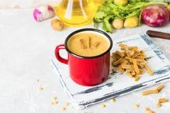 Soupe aux pois avec de la purée de pommes de terre dans la tasse rouge d'émail Photos stock