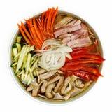 Soupe avec des carottes, des poivrons, des concombres, la viande et des oignons dans un plat sur un fond blanc Images libres de droits