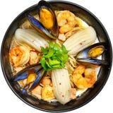 Soupe avec des fruits de mer, calamari, crevette, moules dans un plat noir sur un fond blanc Image stock