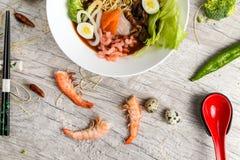 Soupe avec des fruits de mer, des nouilles et des légumes dans un plat blanc photographie stock libre de droits
