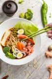 Soupe avec des fruits de mer, des nouilles et des légumes dans un plat blanc photographie stock