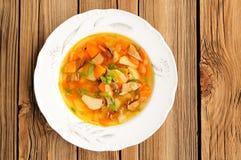 Soupe à champignons de Porcini avec la pomme de terre et la carotte dans le plat blanc sur W Images stock