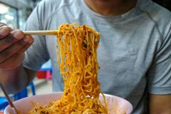 Soupe chaude et aigre à nouille mangeuse d'hommes d'oeufs avec le rôti de porc rouge et le porc croustillant de ventre, nourritur image stock