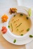 Soupe claire à tomate avec les légumes coupés Image stock