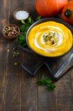 Soupe crème à potiron avec des graines de crème et de citrouille sur la table en bois rustique Photos libres de droits