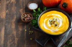 Soupe crème à potiron avec des graines de crème et de citrouille sur la table en bois rustique Photographie stock libre de droits