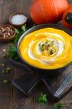 Soupe crème à potiron avec des graines de crème et de citrouille sur la table en bois rustique Images stock