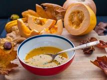 Soupe crème à potiron avec une cuillère de vintage sur un conseil en bois avec images libres de droits